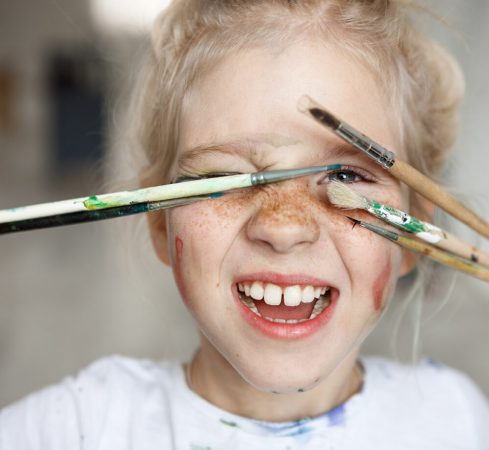Blonde little girl in playful mood with paint on her freckled face and blue eyes covering her face with brushes and looking through them at you like hiding. Playing, smiling child showing her teeth. Positive emotions.